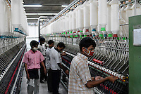 BANGLADESH , textile industry in Dhaka , Beximco textile factory produce Jeans for export for western discounter, spinning unit for production of cotton yarn from cotton fibre/ Bangladesch , Beximco Textilfabrik in Dhaka produziert Jeans fuer den Export fuer westliche Textildiscounter, Spinnmaschinen fuer Herstellung der Baumwollgarne aus Baumwolle