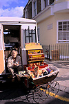Woman with her pet dogs dressed in jumpers in a pram. She is busking she has a old fashioned barrel Organ that she plays. Portobello Road Saturday flea and antique market London 1990s 1999 UK