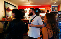"""Justin Boyd talks with attendees of """"Proper Nouns', a photography show by Justin Boyd, at Bankrupt Bodega in the Bloomfield neighborhood on Friday September 3, 2021 in Pittsburgh, Pennsylvania. (Photo by Jared Wickerham/Pittsburgh City Paper)"""