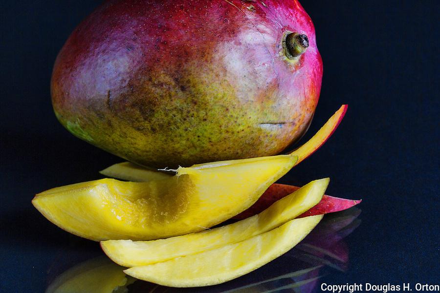 Sliced mango with bite taken.  Black background.