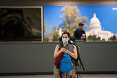 A woman wears a protective mask as she and other passengers arrive from Dubai after a 14-hour flight on Emirates flight 231, at the international terminal at Dulles International Airport in Dulles, Va., Monday, March16, 2020. Some people are taking the precaution of wearing face masks as they arrive to be greeted by family and or friends. Credit: Rod Lamkey / CNP