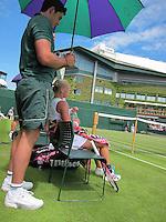 26-06-12, England, London, Tennis , Wimbledon, Kiki Bertens tijdens de wissel, op de achtergrond centercourt