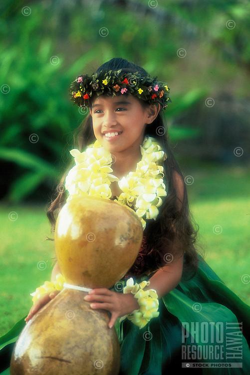 Beautiful young Hawaiian girl (age 7)with ipuheke (gourd), plumeria leis and ti leaf skirt performing a hula noho (seated hula)