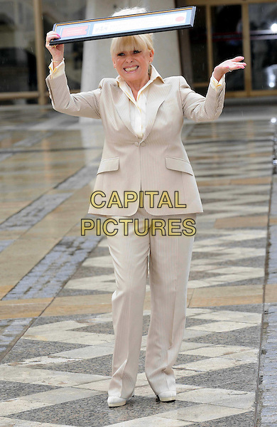 BARBARA WINDSOR.attends a photocall after receiving the Freedom of the City of London at the Guildhall, London, England, UK,.August 4th 2010.full length cream beige suit shirt jacket fringe holding over head raining smiling trousers trouser hand funny .CAP/WIZ.©Wizard/Capital Pictures