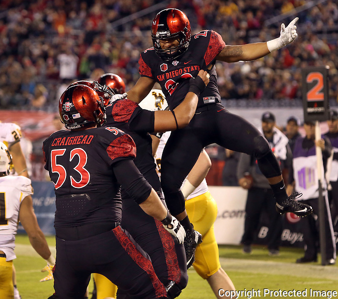 Aztec's  Chase Price celebrates with teammates after scoring in the first quarter against Wyoming Saturday at Qualcomm Stadium. photo by Bill Wechter