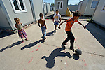 """THIS PHOTO IS AVAILABLE AS A PRINT OR FOR PERSONAL USE. CLICK ON """"ADD TO CART"""" TO SEE PRICING OPTIONS.   Roma children play football amid shipping containers that have been converted into houses in Makis, a village outside of Belgrade, Serbia. These Roma families were evicted from an urban squatter settlement in 2012 to make way for construction of new apartments and office buildings. The shipping containers they now call home, which were provided at no cost by local authorities, are far from the city center."""
