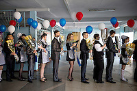 Students who have completed the last year of the secondary schooling line up with bunches of flowers and balloons to celebrate the 'Posledni Zvonok' (Last School Bell) in the village of Yuktali.