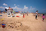 Attentive lifeguards and moms keep an eye on kids playing in the surf at Rehoboth Beach, Delaware, USA.