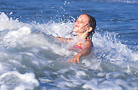 Young girl playing in an ocean wave.