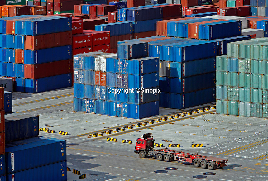 A truck drives past stacks of containers at the Yangshan Deep Water Port near Shanghai, China..