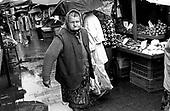 An elderly woman shops in a Krakow food market