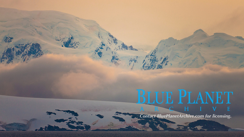 Scenery in Gerlache Strai.  Clouds, mountains, snow, and ocean, at sunset in the Gerlache Strait, Antarctica.