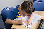 Education Preschool Childcare 2-3 year olds boy signing in for the day by writing in notebook