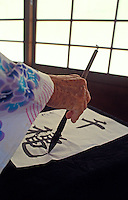 Close-up of a kimono draped arm with hand engaged in calligraphy of Japanese kanji. Shoji screen in background.