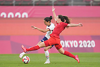 KASHIMA, JAPAN - AUGUST 2: Christen Press #11 of the United States kicks the ball in front of Allysha Chapman #2 of Canada during a game between Canada and USWNT at Kashima Soccer Stadium on August 2, 2021 in Kashima, Japan.