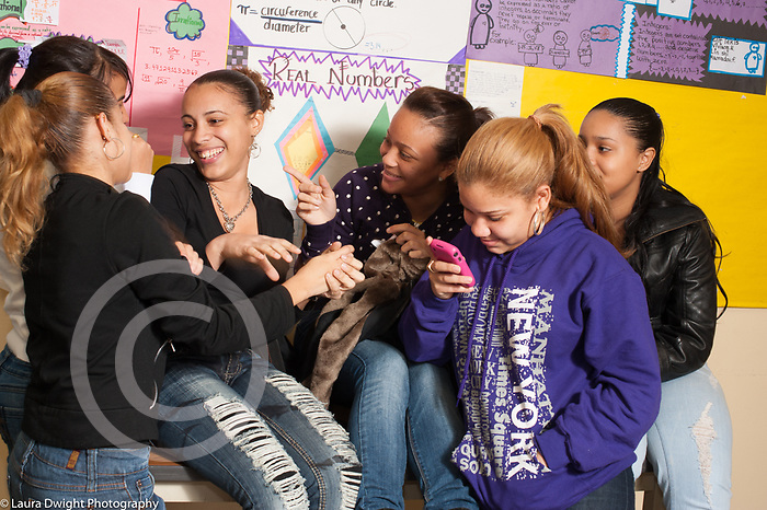 Education High School group of girls in corridor laughing and talking