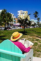 Man with straw hat reading newspaper on a bench on Miami beach road or Ocean Boulevard in Florida, USA