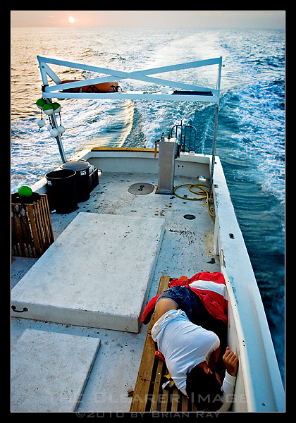 First Mate Travis Lawlor tries to catch up on sleep as The Captain R & R makes its way out to sea at dawn.  Lawlor, who runs his own sport fishing guide service, works for Niklaus on his days off to earn extra money.