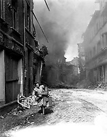 German woman carrying a few possessions runs from burning building in Seigburg, Germany.  Fire started by Nazi saboteur.  April 13, 1945.  T4c. Troy A. Peters, USA. (Roberts Commission)<br /> NARA FILE #:  239-PA-70-4<br /> WAR & CONFLICT BOOK #:  1092