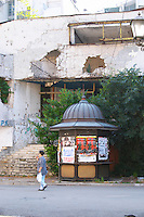 Building in Mostar damaged by the war and still not renovated. Ruined by bullet holes, mortar bomb shell grenade damage, very close to the beautifully renovated old town city centre. An old shopping centre on the Brace Fejica street. An abandoned news stand. A woman walking by. Town of Mostar. Federation Bosne i Hercegovine. Bosnia Herzegovina, Europe.