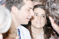 A campaign staffer looks on as Democratic presidential candidate and South Bend mayor Pete Buttigieg greets people and poses for pictures after speaking at a house party with the Bedford Democrats in Bedford, New Hampshire, on Sat., Apr. 20, 2019. The candidate stood on a chair throughout his speech.