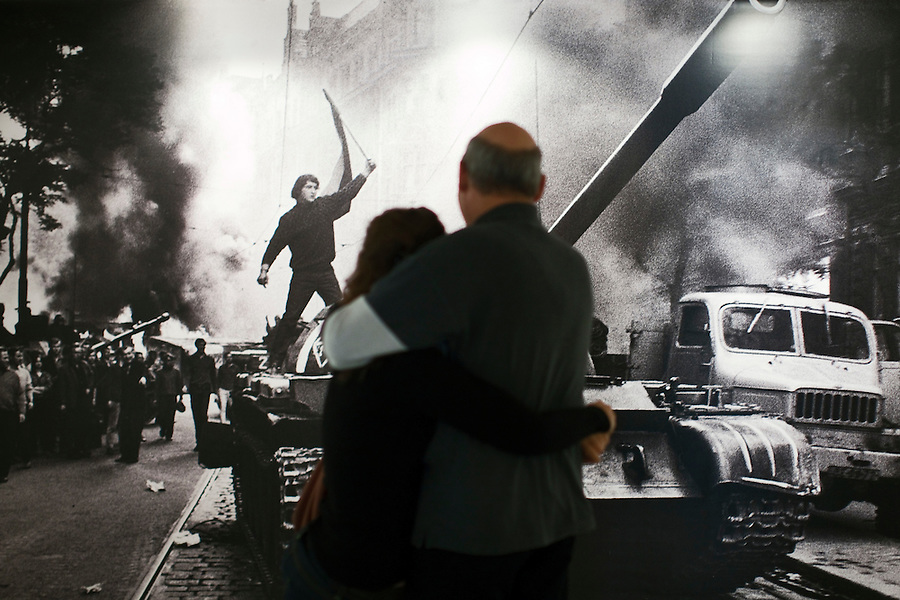 Moscow, Russia, 16/10/2011..A Russian couple embrace at the entrance to Prague Invasion 68, Josef Koudelka's first personal exhibition in Moscow, at the Lumiere Brothers Photography Centre. The pictures, shot during the Soviet invasion of 1968, were smuggled out of Czechoslovakia and at first only published anonymously by Magnum; Koudelka only became publicly known as the photographer some 16 years later.