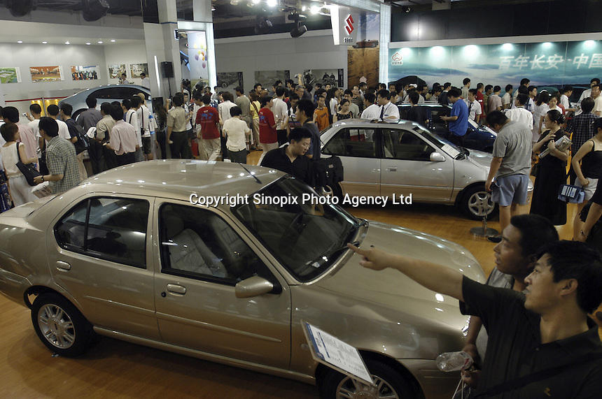 Visitors look at Changan cars at the Auto China 2004 exhibition in Beijing. Changan is a state owned corporation with 23,000 employees, integrating both military and civilian requirements..