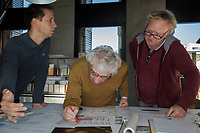 """Switzerland. Canton Ticino. Mendrisio. The architect Mario Botta in his office. Rolls of blueprints with architectural plans and technical drawings of the Basilica """" In the Shrine of our Lady of the Rosary"""" in Namyang, South Korea. Mario Botta draws with a pen on the plan. On the left, his assistant and on the right Ivan Kuntz who has built Botta's architectural models for the last 35 years. 30.10.2017 © 2017 Didier Ruef"""