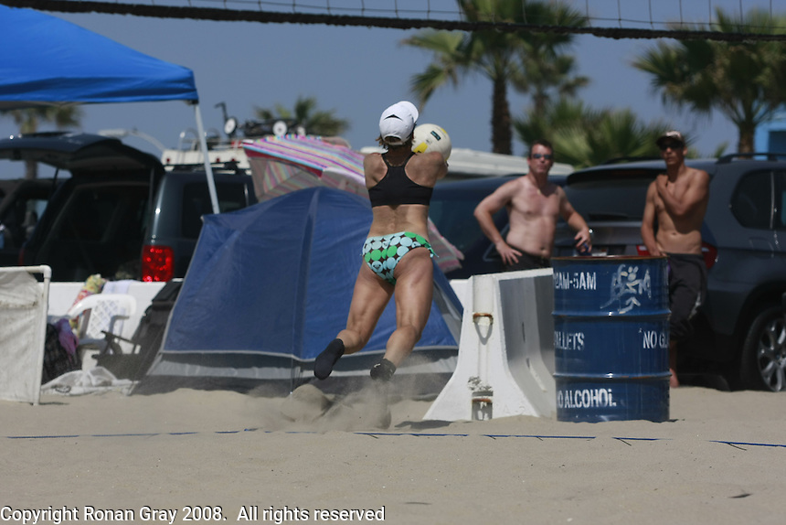 Saturday, May 3 2008 Ocean Beach, San Diego, CA USA.  Diane Johansen is airborne just before colliding with the white concrete barrier in the background during open pool play of the West Coast Volleyball Tournament.  Johansen lost several teeth when she struck the barrier.  She was attended to at the scence by San Diego City Lifeguard Mike Gilmore and another Lifeguard before beign transported to hospital by SDFD Station 15 personnel.   Photo Ronan Gray