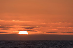 Guadalupe Island, Baja California, Mexico; a large, orange sun setting through the clouds over the pacific ocean