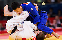 29 JUL 2012 - LONDON, GBR - Cho Jun-Ho (KOR) (top in blue) of South Korea tries to overpower Colin Oates (GBR) of Great Britain during their men's -66kg category repechage contest in the London 2012 Olympic Games judo at the ExCel Exhibition Centre in London, Great Britain (PHOTO (C) 2012 NIGEL FARROW)