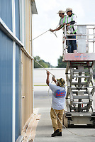 Misael Nieto (from left) paints the lower section Wednesday, September 9, 2020, as Alonso Trujillo and his father Serafin Trujillo, all with Genaro's Painting, work on the upper section of a hanger at the Springdale Municipal Airport. The airport is painting over the blue hangers to match the color of the new hangers built at the airport. Check out nwaonline.com/200910Daily/ and nwadg.com/photos for a photo gallery.<br /> (NWA Democrat-Gazette/David Gottschalk)