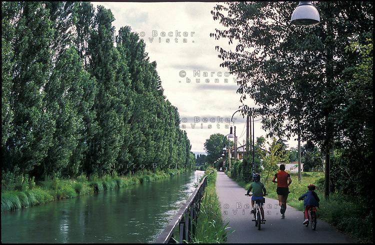 Cernusco sul Naviglio (Milano). Un uomo che corre e due bambini in bicicletta sulla pista ciclabile lungo il Naviglio Martesana --- Cernusco sul Naviglio (Milan). A runner and two kids by bike on the path along the Naviglio Martesana canal