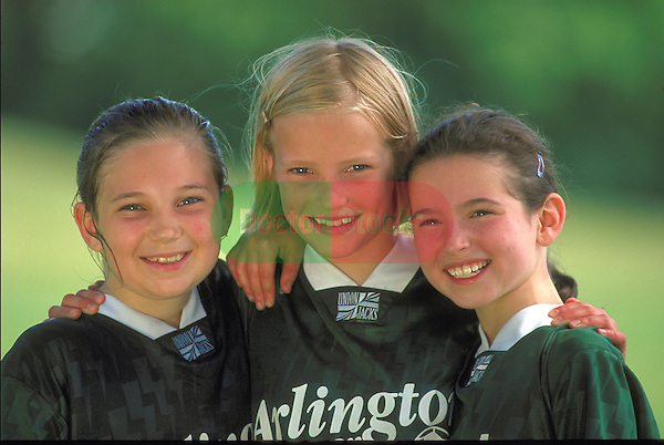 portrait of three smiling girls in soccer uniform