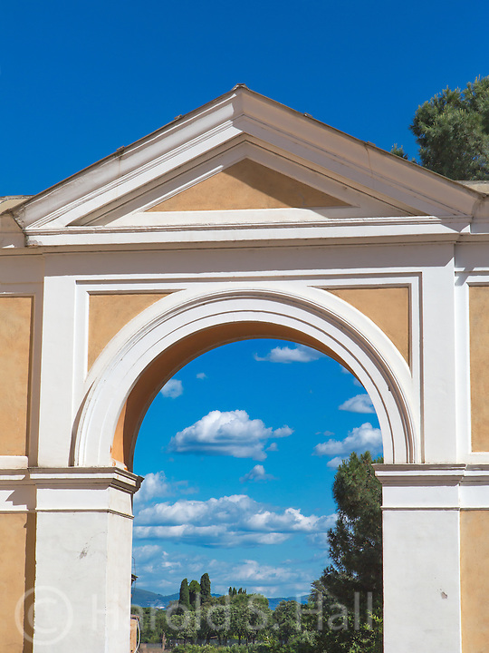 A Roman arch frames the cypress trees and afternoon clouds in Rome, Italy.