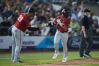 Cal Mitchell (5) of the Altoona Curve slaps hands with third base coach Miguel Perez (29) after hitting a home run against the Somerset Patriots at TD Bank Ballpark on July 24, 2021, in Somerset NJ. (Brian Westerholt/Four Seam Images)