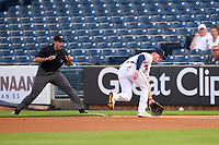 Toledo Mud Hens first baseman Spencer Torkelson (7) fields a ground ball as umpire Alex McKay starts to signal foul ball during a game against the St. Paul Saints on August 26, 2021 at Fifth Third Field in Toledo, Ohio.  (Mike Janes/Four Seam Images)