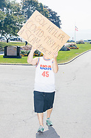 "A man wearing a USA 45 shirt (in reference to the 45th president Donald Trump) holds a piece of wood with the message ""Gov. Hitler / COVID-1984 is a SCAMdeic!!"" as the alt-right organization Super Happy Fun America demonstrates against facemasks, vaccines, and pandemic closures, and in support of the reelection of President Donald J. Trump near the residence of Massachusetts governor Charlie Baker in Swampscott, Massachusetts, on Sat., Sept. 26, 2020. Super Happy Fun America is most well known for organizing the Straight Pride Parade in Boston on August 31, 2019."