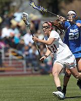 Boston College midfielder Caroline Margolis (21) on the attack as Duke University defender Taylor Virden (23) defends.Boston College (white) defeated Duke University (blue), 10-9, on the Newton Campus Lacrosse Field at Boston College, on April 6, 2013.