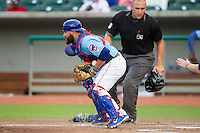 Tennessee Smokies catcher Luis Flores (7) blocks a throw a home plate as home plate umpire David Marcoe looks on during the game against the Mississippi Braves at Smokies Park on July 22, 2014 in Kodak, Tennessee.  The Smokies defeated the Braves 8-7 in 10 innings. (Brian Westerholt/Four Seam Images)