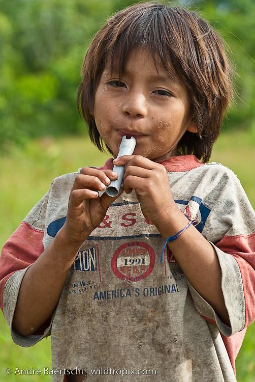 Machiguenga boy playing on a self-made flute, Tayakome native communitiy, lowland tropical rainforest, Manu National Park, Madre de Dios, Peru.