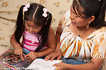 3 year old girl at home with mother looking at picture book