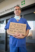 """Corona-Krise - Alltagsheldinnen und Helden.<br /> Im Bild: Thomas F., 52 Jahre, Krankenpfleger im Urban-Krankenhaus in Berlin-Kreuzberg mit einem Schild """"WIR BLEIBEN fuer euch da!! BLEIBT ihr bitte fuer uns DAHEIM"""".<br /> 25.3.2020, Berlin<br /> Copyright: Christian-Ditsch.de<br /> [NUR FUER REDAKTIONELLE ZWECKE! Werbung nur auf Anfrage beim Fotografen. Inhaltsveraendernde Manipulation des Fotos nur nach ausdruecklicher Genehmigung des Fotografen. Vereinbarungen ueber Abtretung von Persoenlichkeitsrechten/Model Release der abgebildeten Person/Personen liegen nicht vor. NO MODEL RELEASE! Don't publish without copyright Christian-Ditsch.de, Veroeffentlichung nur mit Fotografennennung, sowie gegen Honorar, MwSt. und Beleg. Konto: I N G - D i B a, IBAN DE58500105175400192269, BIC INGDDEFFXXX, Kontakt: post@christian-ditsch.de<br /> Bei der Bearbeitung der Dateiinformationen darf die Urheberkennzeichnung in den EXIF- und  IPTC-Daten nicht entfernt werden, diese sind in digitalen Medien nach §95c UrhG rechtlich geschuetzt. Der Urhebervermerk wird gemaess §13 UrhG verlangt.]"""