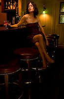 A model poses with a drink in hand at the bar in Maine.
