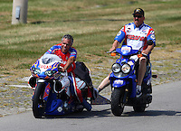 Aug. 31, 2013; Clermont, IN, USA: NHRA pro stock motorcycle rider Hector Arana Sr (left) with a crew member during qualifying for the US Nationals at Lucas Oil Raceway. Mandatory Credit: Mark J. Rebilas-