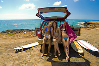 Three young women with surfboards sitting in a car at Makaha