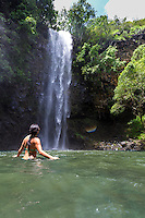 A woman soaks in the sun and water at Uluwehi Falls, Kaua'i.