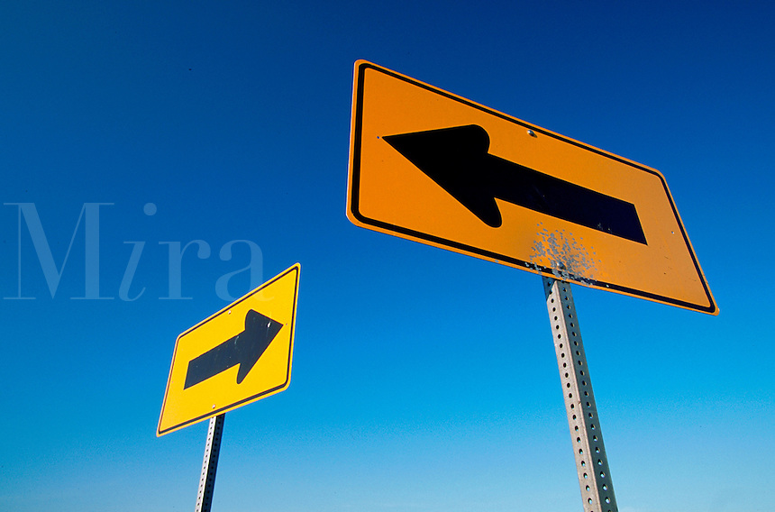 Abstract graphic of road signs (arrows) pointing left and right under, and in bold contrast to the deep blue sky.