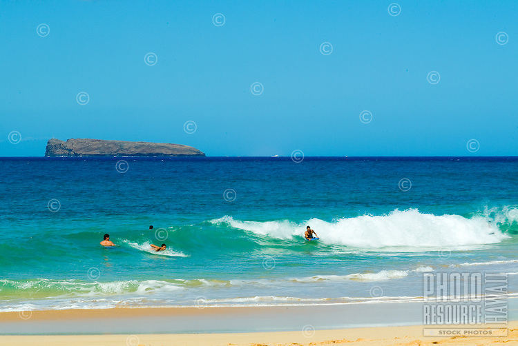 Body boarders enjoy the waves at beautiful  Makena Beach on Maui, also known as Big Beach. Molokini in background.
