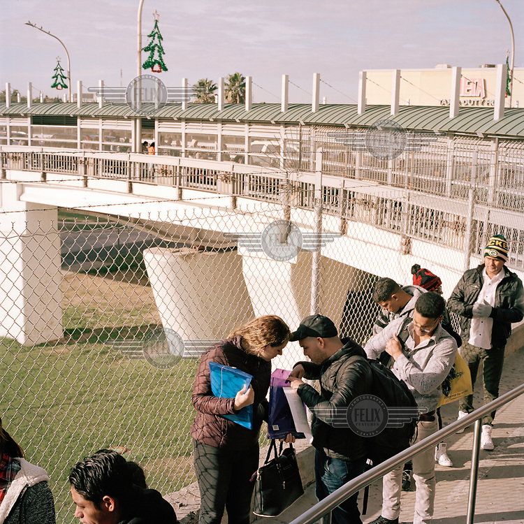 A small group of foreign nationals wait to meet with US Customs and Border Patrol officers on top of the bridge over the Rio Bravo/Rio Grande, between Laredo (in the USA) and Nuevo Laredo (in Mexico).